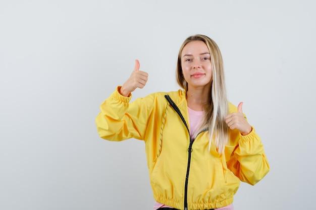 Blond meisje in t-shirt, jas met dubbele duimen omhoog en ziet er vrolijk uit