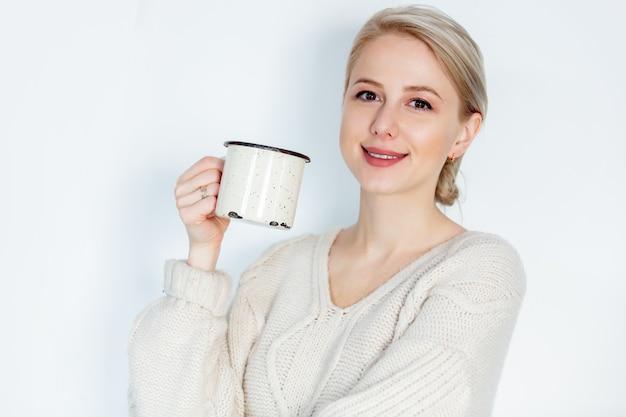 Blond meisje in trui met mok op wit
