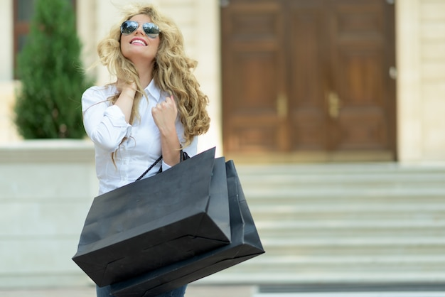 Blond meisje in zonnebril met boodschappentassen op straat
