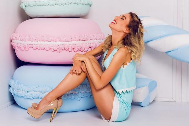 Blond meisje in zonnebril met mooie huid en lippen, poseren in studio, zittend op de vloer, lachen. het dragen van vintage hart zonnebril, stijlvolle blauwe lederen top.