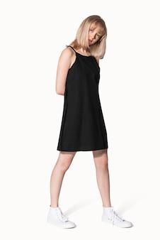 Blond meisje in zwarte a-lijn jurk voor zomerkledingshoot voor tieners