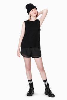 Blond meisje in zwarte tanktop en korte broek met muts voor street fashion shoot