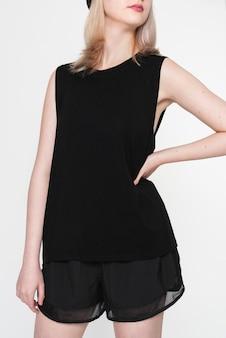 Blond meisje in zwarte tanktop en korte broek voor street fashion shoot