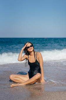 Blond meisje in zwempak dat het op zee strand looien zit