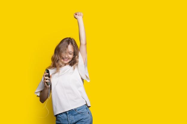 Blond meisje juicht op een gele muur met vrije ruimte terwijl ze naar muziek luistert op oortelefoons en haar hand omhoog houdt