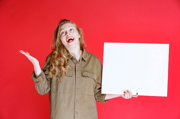 Blond meisje kijkt naar een canvas en wordt verrast.