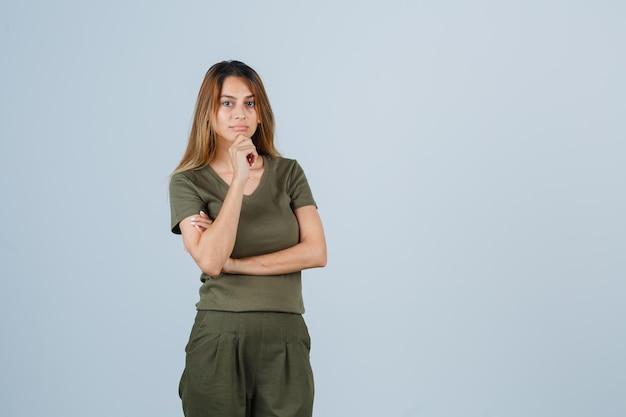 Blond meisje leunt wang op palm terwijl ze aan iets denkt in olijfgroen t-shirt en broek en peinzend kijkt. vooraanzicht.