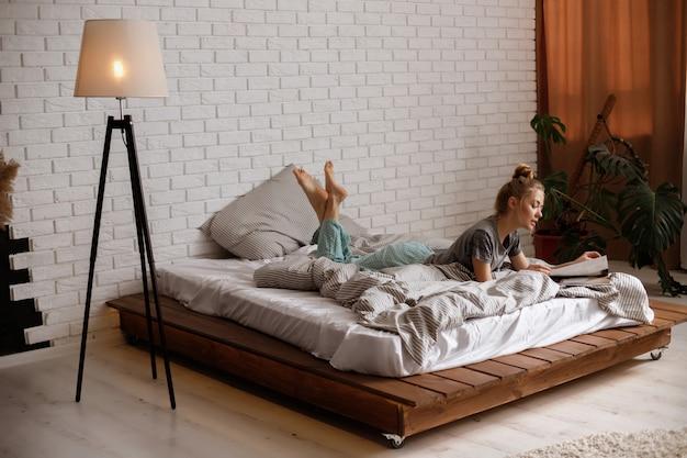 Blond meisje ligt op het bed en het lezen van een tijdschrift. stijlvol slaapkamerinterieur met model