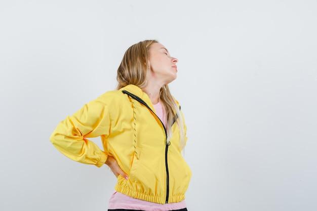 Blond meisje lijdt aan rugpijn in gele jas en ziet er vermoeid uit.