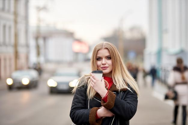 Blond meisje loopt door de stad en drinkt koffie