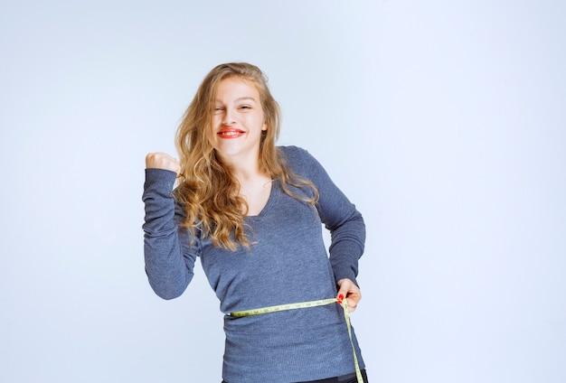 Blond meisje meet haar tailleomvang met een tape en voelt zich succesvol.