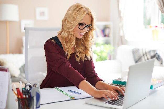 Blond meisje met behulp van laptop tijdens thuis studeren