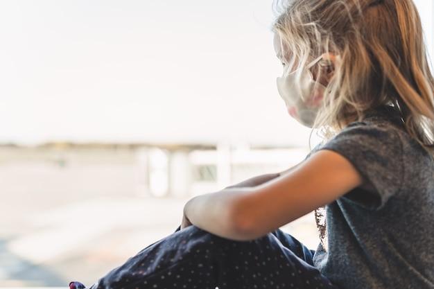 Blond meisje met beschermend masker op haar gezicht kijkt verdrietig door het raam op de luchthaven op vliegtuigen. reizen, pandemie, kindertijd, nieuwe norm.