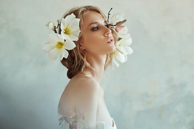 Blond meisje met bloemen in de buurt van het gezicht