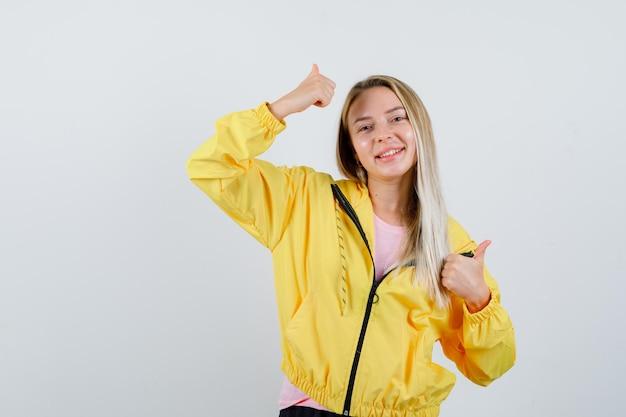 Blond meisje met dubbele duimen omhoog in t-shirt, jas en vrolijk.