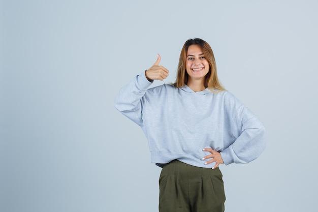 Blond meisje met duim omhoog en hand op taille in olijfgroen blauw sweatshirt en broek en ziet er gelukkig uit. vooraanzicht.