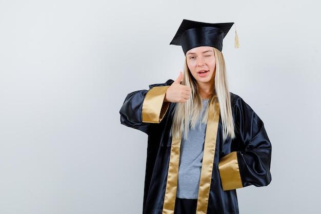 Blond meisje met duim omhoog terwijl ze de hand op de taille houdt, knipogend in afstudeerjurk en pet