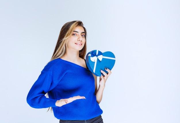 Blond meisje met een blauwe geschenkdoos in de vorm van een hart.
