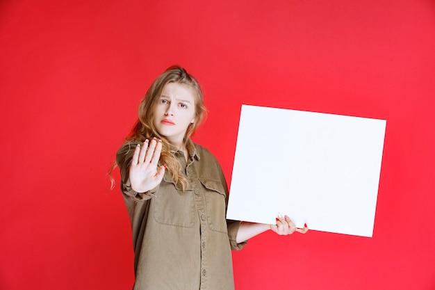 Blond meisje met een canvas en ziet er ontevreden uit.