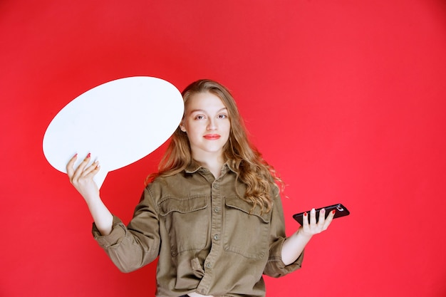 Blond meisje met een ovale ideaboard in de ene hand en een smartphone in de andere hand.