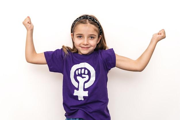 Blond meisje met een paars t-shirt met het symbool van de internationale feministische vrouwendag op een witte muur, haar armen omhoog houdend