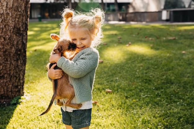 Blond meisje met een puppy buitenshuis