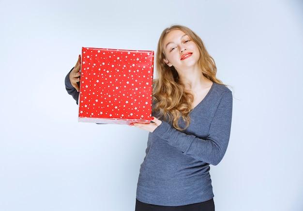 Blond meisje met een rode grote geschenkdoos.