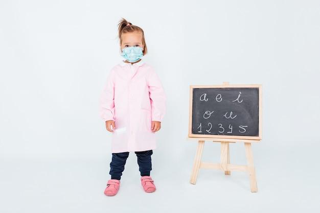 Blond meisje met een roze kinderschort en een chirurgisch masker om zichzelf tegen covid-19 te beschermen