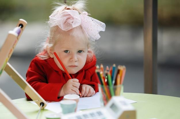 Blond meisje met een strik trekt met potloden.