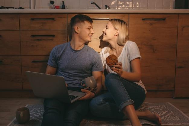 Blond meisje met een taart en lacht naar haar minnaar zittend op de vloer in de keuken
