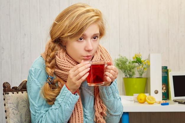 Blond meisje met een verkoudheid in een trui die hete thee drinkt, op een tafel, uien, citroenen, boeken en een laptop