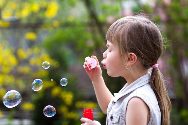 Blond meisje met ernstige uitdrukking blazen kleurrijke transparante zeepbellen