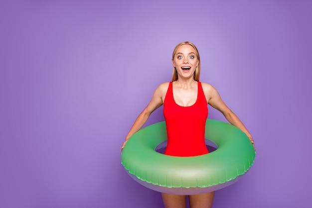 Blond meisje met groene vlotter rond taille geïsoleerd op paars