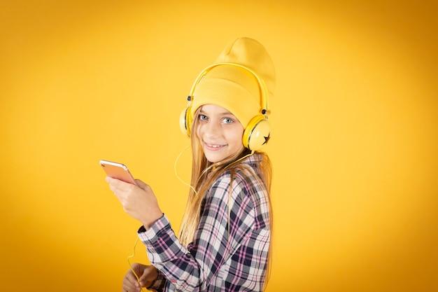 Blond meisje met hoed en koptelefoon luisteren naar muziek met haar mobiele, gele muur