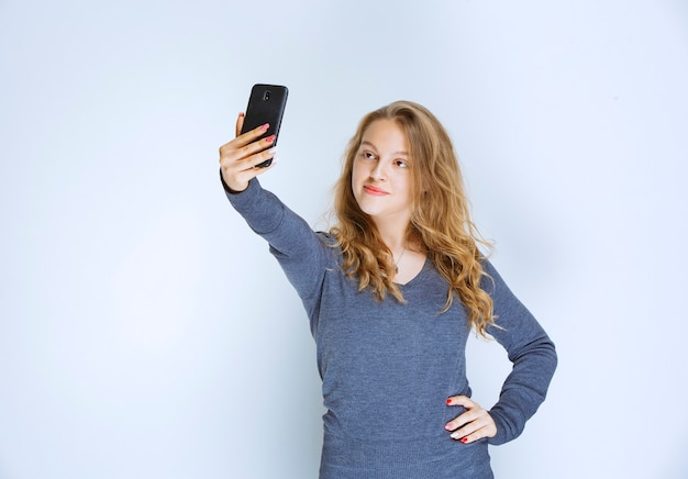 Blond meisje met krullend haar dat haar selfie neemt.