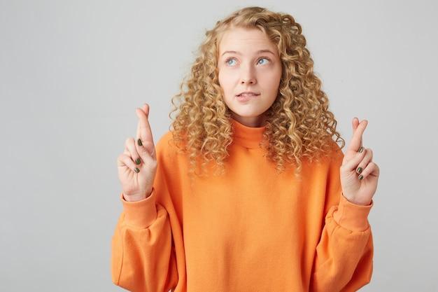 Blond meisje met krullend haar in een feloranje trui kijkt in de linkerbovenhoek en houdt vingers gekruist terwijl ze op haar lip bijt, doe een wens