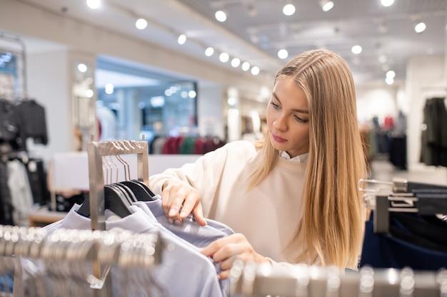 Blond meisje met lang haar kijken door collectie shirts op rek tijdens het zoeken naar haar maat tijdens seizoensuitverkoop