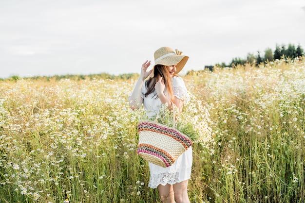 Blond meisje met madeliefjebloemen. zomervakantie. platteland. vrijheid en hete zomer