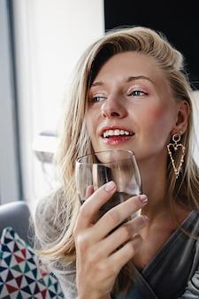 Blond meisje met mooi haar en make-up glimlachend met een glas water te drinken en een tost op vakantie voor te stellen.