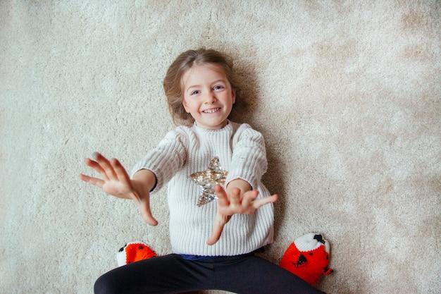 Blond meisje met plezier met mama op het tapijt