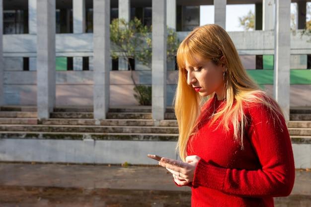 Blond meisje met rode lippenstift en rode trui browsen met haar telefoon in een park.