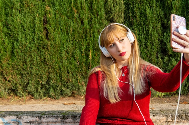 Blond meisje met rode lippenstift en rode trui doet zelf een foto met koptelefoon in het park.