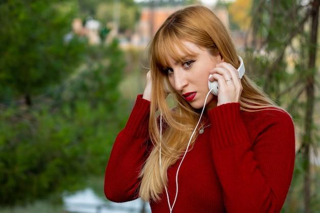 Blond meisje met rode lippenstift en rode trui, luisteren naar muziek met een koptelefoon in het park.