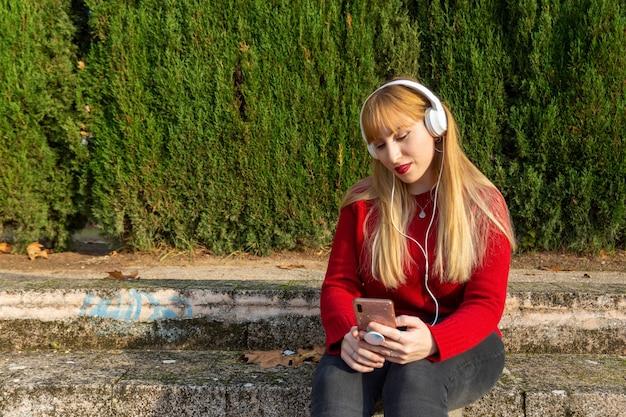 Blond meisje met rode lippenstift en rode trui, luisteren naar muziek met telefoon en koptelefoon in het park.