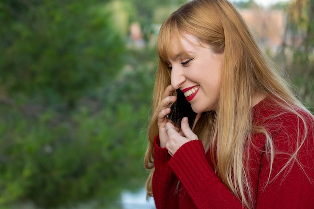 Blond meisje met rode lippenstift en rode trui praten over haar mobiele telefoon.