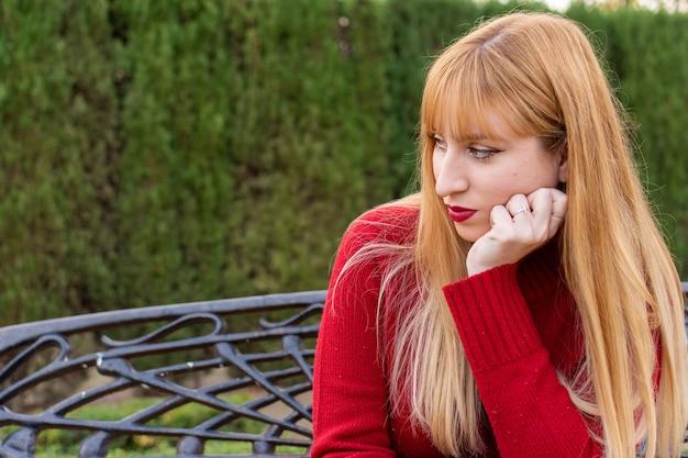 Blond meisje met rode lippenstift en rode trui zitten in een park. verveeld en denken.