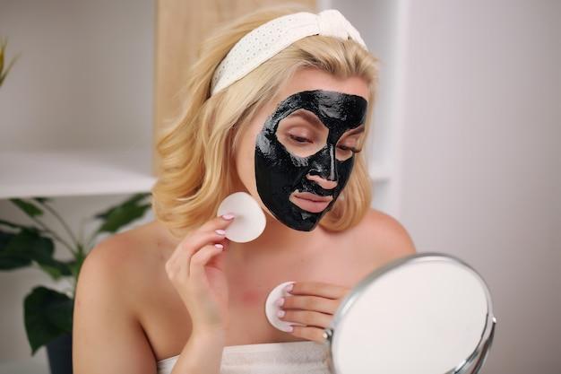 Blond meisje met spons om lotion thuis toe te passen