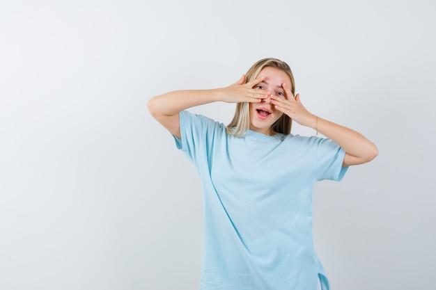 Blond meisje met v-tekens op ogen in blauw t-shirt en ziet er mooi uit, vooraanzicht.
