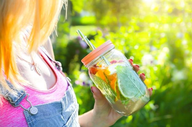 Blond meisje met verse limonade in pot met stro. hipster zomerdrankjes. gezonde veganistische levensstijl. milieuvriendelijk in de natuur. citroenen, sinaasappelen en bessen met munt in het glas.
