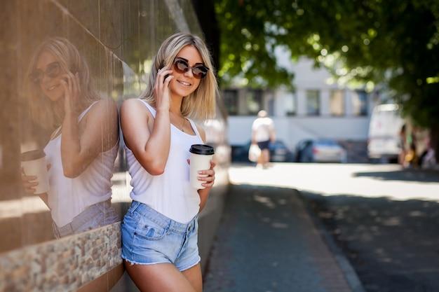 Blond meisje met zonnebril praten over de telefoon en het hebben van een kopje koffie in haar hand